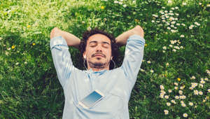 Relaxed man lying down at the meadow and listening to music.