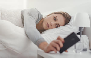 Woman waking up in her bed and taking her smartphone, she is checking messages and snoozing alarm