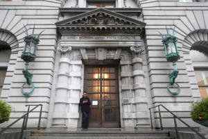 FILE - In this Feb. 9, 2017 file photo, a man stands outside the main door outside the 9th U.S. Circuit Court of Appeals building in San Francisco. (AP Photo/Marcio Jose Sanchez, File)