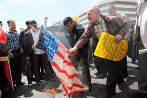 Iranian worshippers burn a US flag in Tehran after prayer.