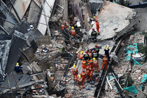 Members of a rescue team work at the site of a building collapse in Shanghai on May 16, 2019. At least ten construction workers were trapped in the rubble of an industrial building that collapsed in Shanghai on May 16 as it was undergoing renovation, according to Chinese media reports.