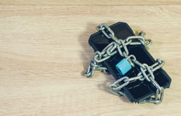chain locked on phone concept for security on smart phone.On the wooden floor