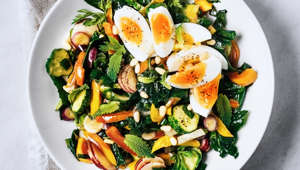 A bowl of fresh salad with boiled eggs on white background