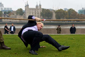 """LONDON, ENGLAND - OCTOBER 27:  Mayor of London Boris Johnson slips over while competing in a tug of war during the launch of London Poppy Day on October 27, 2015 in London, England. Poppies have been used to commemorate soldiers who have died in conflict since 1914 and are distributed by the British Royal Legion in the UK in return for donactions to the """"Poppy Appeal"""".  (Photo by Ben Pruchnie/Getty Images)"""