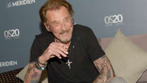 French singer Johnny Hallyday smiles as he speaks to journalists in the Le Meridien hotel in Noumea on April 29, 2016 before his concert. / AFP PHOTO / Fred Payet        (Photo credit should read FRED PAYET/AFP/Getty Images)