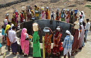 Indian women from the aboriginal 'Kol' community collect drinking water at a well in Nawargawa village, some 30km from Jabalpur, in Madhya Pradesh state on June 16, 2019. - Around 40 families in the village rely on the well for drinking water during the heatwave conditions in the remote central Indian region. (Photo by Uma Shankar MISHRA / AFP)        (Photo credit should read UMA SHANKAR MISHRA/AFP/Getty Images)