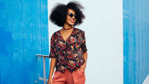 Gorgeous young african american girl in sunglasses, posing outdoors, keeping her hand in pocket. Dressed in bright blouse and pants, with short voluminous hair.