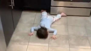 Toddler catches some shut-eye on the kitchen floor