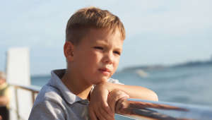 Little kid looking at the sea from the railing of a cruise. Portrait of cute little boy posing at metal fence.