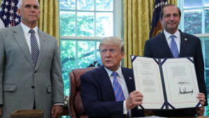 U.S. President Donald Trump holds up border funding legislation as Vice President Mike Pence and Health and Human Services (HHS) Secretary Alex Azar stand by during a signing ceremony in the Oval Office of the White House in Washington, U.S. July 1, 2019. REUTERS/Jonathan Ernst