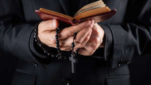 Religious person studies Bible and holds prayer beads, low-key image