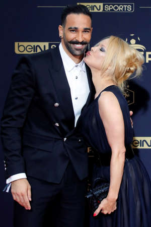 Soccer player Adil Rami and US actress Pamela Anderson pose as they arrive at the UNFP (Union of French Professional Footballers) ceremony, in Paris, France, Sunday, May 19, 2019. (AP Photo/Francois Mori)