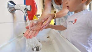 A woman shows a child how to wash his hands with an antibacterial hand gel, on August 28, 2009, at the Sainte Marie Institute, in Caen, northwestern France. The doses of swine flu vaccine to combat the pandemic arrived as millions of schoolchildren prepared to return to school in the next two weeks, with concerns that the virus could spread easily between classrooms. AFP PHOTO / MYCHELE DANIAU (Photo credit should read MYCHELE DANIAU/AFP/Getty Images)