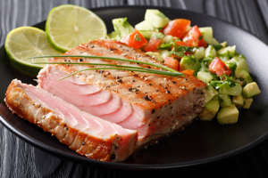 Barbecue tuna steak with lime and avocado cucumber salsa closeup on a plate. horizontal