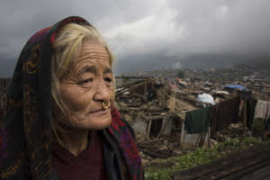 BARPAK, NEPAL - MAY 1, 2015:  Dhan Maya Ghale,68 stands next to her destroyed home in Barpak on May 1, 2015 where 60% of the village has been destroyed. The village is amongst the largest in Gorkha province with a population of around 10-12,000. The April 25th earthquake with a magnitude of 7.8  killed over 9,000 in Nepal's worst earthquake in 80 years.  (Photo by Paula Bronstein/ Getty Images)