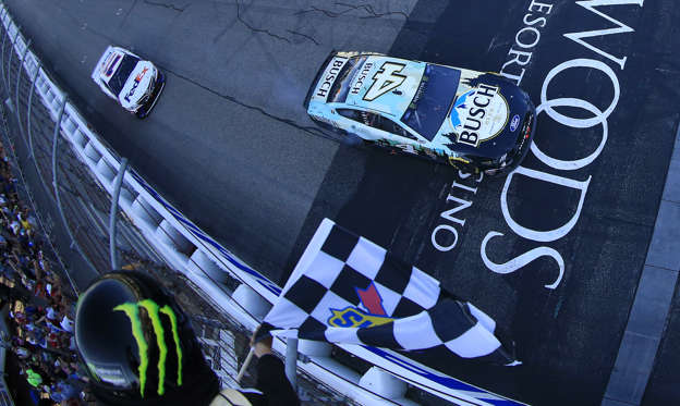 LOUDON, NEW HAMPSHIRE - JULY 21:  Kevin Harvick, driver of the #4 Busch Beer/National Forest Foundation Ford, takes the checkered flag in front of Denny Hamlin, driver of the #11 FedEx Express Toyota,  to win the Monster Energy NASCAR Cup Series Foxwoods Resort Casino 301 at New Hampshire Motor Speedway on July 21, 2019 in Loudon, New Hampshire. (Photo by Chris Trotman/Getty Images)