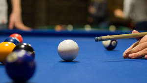 Representational Image- Billiard pool game in progress, player aims to shoot balls with cue
