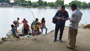 A man from Guatemala shows his ID to an agent of the National Immigration Institute (INM) after crossing on a raft from Tecun Uman, Guatemala, to Ciudad Hidalgo, Mexico, as seen from Ciudad Hidalgo, Mexico, July 16, 2019. REUTERS/Jose Torres