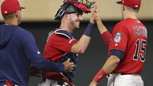 Minnesota Twins' catcher Mitch Garver, center, is congratulated by fellow catcher Jason Castro, right, after they defeated the New York Yankees in a baseball game Monday, July 22, 2019, in Minneapolis. Garver had two home runs in the game. (AP Photo/Jim Mone)