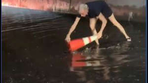 Woman clears clogged drains during flash floods