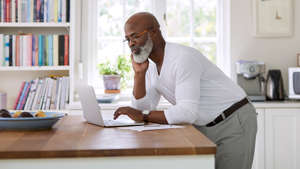 a man sitting at a table looking at a book: The 2018 inflation rate is 2.38 percent, and it's projected to range from 2.18 percent to 2.64 percent over the next few years, according to Statista. Although the inflation rate might seem minimal, it still affects how far your dollar will go. This is especially true for money held in fixed savings accounts, which unlike money in certain investments, will lose value over time.