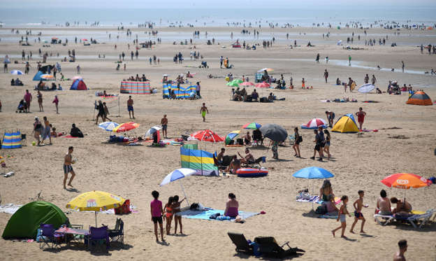 Slide 1 of 31: Beach-goers shelter enjoy the sunshine by the sea in Camber Sands, southern England on July 25, 2019, during a heatwave in Britain. (Photo by Ben STANSALL / AFP)        (Photo credit should read BEN STANSALL/AFP/Getty Images)