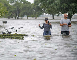 Collen Schiller and Wesley Vinson wade through storm surge from Lake Pontchartrain on Lakeshore Drive in Mandeville, La., Saturday, July 13, 2019. The waves are caused by the wind and storm surge from Hurricane Barry in the Gulf of Mexico. Mandeville is on the north shore of the lake while New Orleans is on the south shore. (AP Photo/Matthew Hinton)