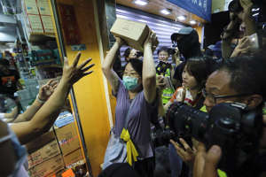 A protester throws a box of goods at a store that sells to mainland customers, in Hong Kong, July 13. Several thousand people marched in Hong Kong on Saturday against traders from mainland China in what is fast becoming a summer of unrest in the semi-autonomous Chinese territory.