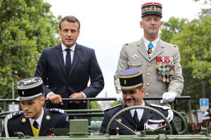 France's President Emmanuel Macron stands in an Acmat VLRA vehicle next to French army's chief of staff General Francois Lecointre as they review troops before the start of the Bastille Day military parade down the Champs-Elysees avenue in Paris, France July 14, 2019. Ludovic Marin/Pool via REUTERS