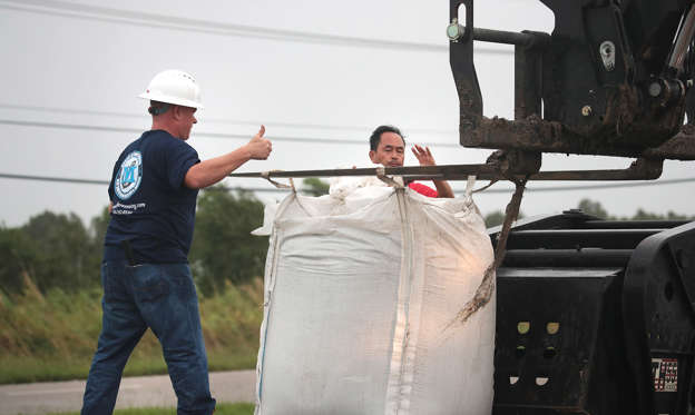 Slide 1 of 76: Workers use giant sandbags to raise a levee that was topped during Hurricane Barry on July 14, 2019 in Myrtle Grove, Louisiana. The storm, which made landfall yesterday as a category one hurricane near Morgan City, caused far less damage than had been predicted but bands of rain and thunderstorms continue to soak the area and cause flash-flood concerns.
