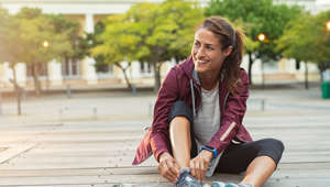 Mature fitness woman tie shoelaces on road. Cheerful runner sitting on floor on city streets with mobile and earphones wearing sport shoes. Active latin woman tying shoe lace before running.