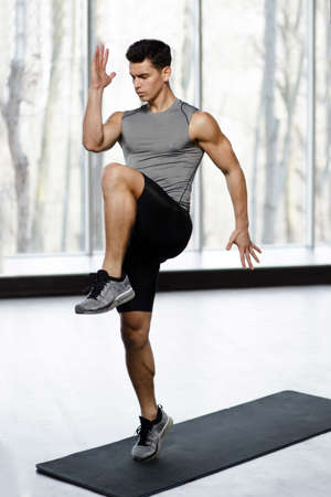 Profile image of athletic young man in sportswear doing strength exercise with legs in gym, isolated on a big window background. Sporty concept.