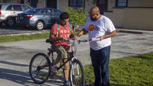Carlos Naranjo, right, gives Michael Cruz a know-your-rights flyer in Pompano Beach, Fla., on Sunday, July 14, 2019. The handout explains what rights undocumented immigrants have in case they encounter ICE officials. Cruz is not undocumented. (Charlie Ortega Guifarro/Miami Herald/TNS via Getty Images)