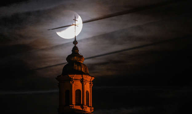 Lysbilde 1 av 28: 16 July 2019, Baden-Wuerttemberg, Weingarten: The partly hidden moon can be seen behind the basilica, while an airplane flies by in front of the moon. Photo: Felix Kästle/dpa (Photo by Felix Kästle/picture alliance via Getty Images)
