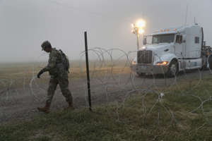 FILE: A U.S. Army soldier opens a gate while on guard duty near the U.S.-Mexico border on November 5, 2018 in Donna, Texas. Troops had set up razor wire there in previous days to secure an area for tent construction. (Photo by John Moore/Getty Images)
