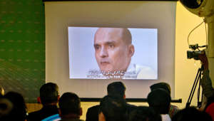 In this March 29, 2016 photo, journalists look a image of Indian naval officer Kulbhushan Jadhav,  who was arrested in March 2016, during a press conference by Pakistan's army spokesman and the Information Minister, in Islamabad, Pakistan. The army said in a statement Monday, April 10, 2017, that Jadhav was sentenced to death on charges of espionage and sabotage. Pakistan says Jadhav was an Indian intelligence official who aided and financed terrorist activities. (AP Photo/Anjum Naveed)