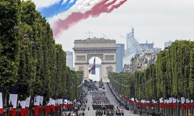 Slide 1 of 32: French Alpha jets of the Patrouille de France spray lines of smoke in the colors of the French flag over the Champs-Elysees avenue during the Bastille Day parade in Paris, France, Sunday, July 14, 2019. (AP Photo/Michel Euler)