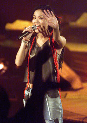 KUALA LUMPUR, MALAYSIA:  Hong Kong pop star Faye Wong waves to fans during the first night of her two-day concert in Kuala Lumpur 21 August 1999.  Tickets were sold out for the performance.      (ELECTRONIC IMAGE)  AFP PHOTO/Jimin LAI (Photo credit should read JIMIN LAI/AFP/Getty Images)