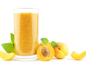 a glass of orange juice: Apricot-Mango Madness