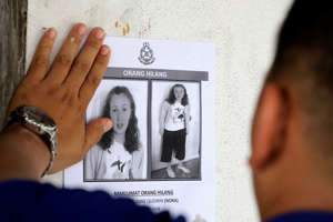 A police officer paste a photo of 15-year-old Irish girl Nora Anne Quoirin who went missing from a resort on a wall at a shop in Seremban, Malaysia, August 9, 2019. REUTERS/Lim Huey Teng