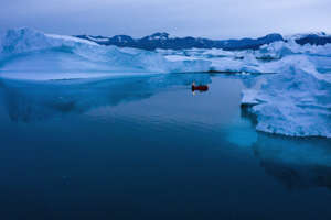 FILE PHOTO - A boat navigates at night between icebergs in eastern Greenland, late Friday, Aug. 15, 2019. Greenland has been melting faster in the last decade and this summer, it has seen two of the biggest melts on record since 2012. (AP Photo/Felipe Dana)