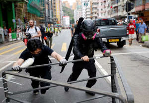 A protester nicknamed Ah Lung and another protester push a barricade to the frontline during a protest in Sham Shui Po neighbourhood of Hong Kong, China.