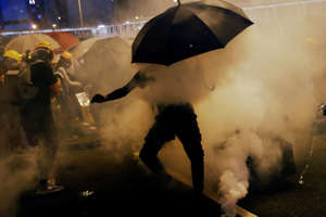 Pro-democracy protesters use umbrellas to protect themselves from tear gas during a protest against police violence during previous marches, near China's Liaison Office, Hong Kong, China July 28, 2019.