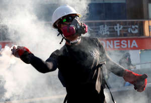 A protester throws a tear gas canister back at the police during a demonstration in support of the city-wide strike and to call for democratic reforms in Hong Kong, China.
