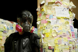 """A protester nicknamed Ah Lung poses before sticky note mosaics dubbed as """"Lennon Wall"""" in Sha Tin district of Hong Kong, China."""