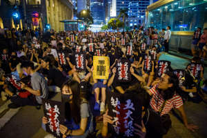 "16 August 2019, China, Hongkong: A participant holds a sign (""Power to the People"") up in front of the Chater Garden in Hong Kong's Central District during a protest rally. Despite open threats from Beijing with military force, there were new protests in Hong Kong on Friday. In the former British colony, which belongs to China as a special administrative zone, it is estimated that in the evening more than 25,000 people took to the streets again peacefully for freedom and democracy. Photo: Gregor Fischer/dpa (Photo by Gregor Fischer/picture alliance via Getty Images)"