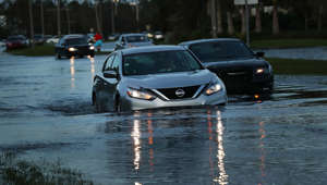 BONITA SPRINGS, FL - SEPTEMBER 11: Cars make their away through a flooded street the morning after Hurricane Irma swept through the area on September 11, 2017 in Bonita Springs, Florida. Hurricane Irma made another landfall near Naples yesterday after inundating the Florida Keys. Electricity was out in much of the region with localized flooding.  (Photo by Spencer Platt/Getty Images)