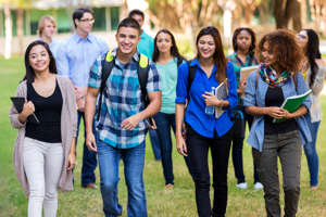 Diverse group of young adult and teenage college students are smiling while walking together outdoors on school campus. Hispanic, Caucasain, and African American students are wearing backpacks, trendy clothing, and are carrying school books.