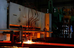 A slab of newly formed steel is cut into sections at the U.S. Steel Granite City Works facility Thursday, June 28, 2018, in Granite City, Ill. (AP Photo/Jeff Roberson)