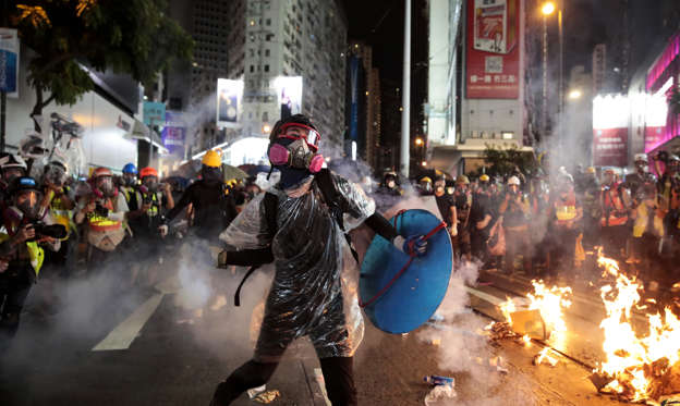 Slide 1 of 50: A protestor hurls back an exploded tear gas shell at police officers on Aug. 31.